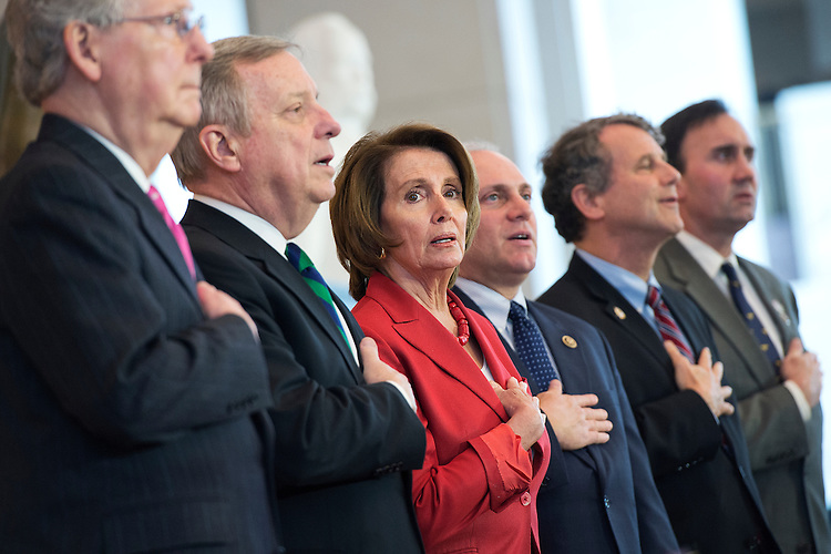 UNITED STATES - APRIL 15: From left, Senate Majority Leader Mitch McConnell, R-Ky., Senate Minority Whip Richard Durbin, D-Ill., House Minority Leader Nancy Pelosi, D-Calif., House Majority Whip Steve Scalise, R-La., Sen. Sherrod Brown, D-Ohio, and Rep. Pete Olson, R-Texas, sing the National Anthem during a Congressional Gold Medal ceremony to honor the Doolittle Tokyo Raiders in the Capitol Visitor Center's Emancipation Hall, April 15, 2015. (Photo By Tom Williams/CQ Roll Call)