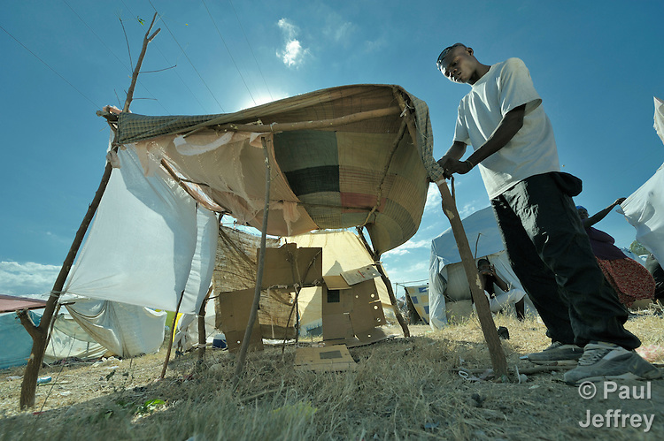 A man fastens together a temporary shelter for his family in a spontaneous camp for quake survivors being established in Croix-des-Bouguets, Haiti, north of the capital Port-au-Prince. Quake survivors continue to move as aftershocks continue, and reports of aid deliveries in one camp will provoke families from other camps to migrate there.