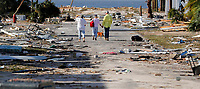 People hold hands as they walk amidst destruction in the aftermath of Hurricane Michael in Mexico Beach, Fla., Thursday, Oct. 11, 2018. (AP Photo/Gerald Herbert)