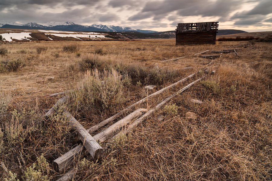 A decaying cabin and fence sit in a dry prairie near the Anaconda area of Montana on an early Spring morning.