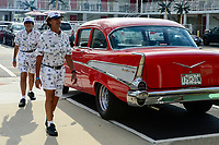 USA, New Jersey, Wildwood, parade of classic cars, GM General Motors Chevrolet Bel Air at parking place of Motel and two walking guys in white partner look with shorts and USA cap, could be in Havanna Cuba too