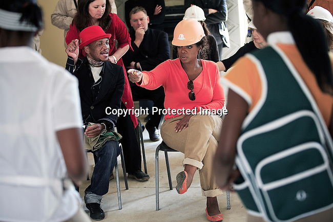 """JOHANNESBURG, SOUTH AFRICA AUGUST 10: Oprah Winfrey inspects school uniforms being modeled at the site of her school """"Oprah Winfrey Leadership Academy for Girls"""" located about 40 miles south of Johannesburg in Henley-on-Klip, Meyerton. Oprah visited South Africa to interview girls and to inspect the construction of the school. .(Photo by Per-Anders Pettersson)."""