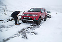 22/01/19<br /> <br /> A man digs tracks into the snow give a 4x4 pick more traction before towing a stuck Jaguar near to Mam Tor and near Castleton in the Derbyshire Peak District.<br /> <br /> All Rights Reserved, F Stop Press Ltd +44 (0)7765 242650  www.fstoppress.com rod@fstoppress.com