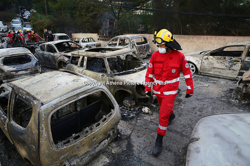 Pictured: Firemen search through burned cars in the Mati area, Kokkino Limanaki near Rafina, Greece. Tuesday 24 July 2018<br /> Re: Deaths caused by wild forest fires throughout Greece.