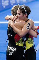 12 JUL 2014 - HAMBURG, GER - German team mates Rebecca Robisch (GER) (left) and Anja Knapp (GER) (right) support each other at the finish of the elite women's 2014 ITU World Triathlon Series round in the Altstadt Quarter in Hamburg, Germany (PHOTO COPYRIGHT © 2014 NIGEL FARROW, ALL RIGHTS RESERVED)