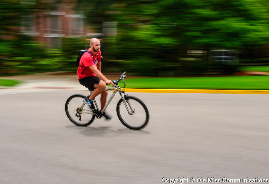 A cyclist zips down University Avenue toward the Circle. Photo by Robert Jordan/Ole Miss Communications