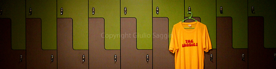 A Goodies T-shirt hangs on the front of a locker in a change room.