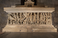 St Sernin arrested in Toulouse by Roman soldiers (right) and a bull dragging his body through Toulouse (left), on the sarcophagus of St Sernin, by the Master of Cabestany in Romanesque style, mid 12th century, in the Saint-Hilaire-D'Aude Abbey, built 11th - 14th centuries and closed 1748, when it became a parish church, Saint-Hilaire, Aude, Languedoc-Roussillon, France. The Roman soldiers have monstrous animals between their legs representing evil. People watch the scene from their windows, and on the right an acrobat on his rope stops to look. St Hilary built the first chapel on this site in the 6th century, dedicated to St Sernin. In the 10th century his relics were discovered here and the church, then an abbey, rededicated to St Hilaire. Picture by Manuel Cohen
