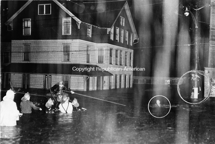 This scene shows a rescue that occurred at the height of the storm at Riverside and Summit streets. Deputy Fire Chief Frank Moore, white coat and waist-deep in flood water, and Battalion Chief Walter Joy, directly ahead of him, direct a rescue operation of three stranded Waterbury firemen. Private William O'Neill, on the fence post, guides Private George Brown from the pole across the raging current. The house at left was later swept away.