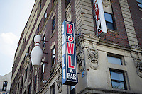 A bowling pin and sign on the facade of a building advertise a bowling alley that is no longer there in the neighborhood of Harlem in New York on Sunday, June 23, 2013.  (© Frances M. Roberts)