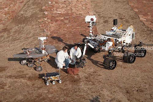 "Two spacecraft engineers join a grouping of vehicles providing a comparison of three generations of Mars rovers developed at NASA's Jet Propulsion Laboratory, Pasadena, California on December 15, 2011. The setting is JPL's Mars Yard testing area.  Front and center is the flight spare for the first Mars rover, Sojourner, which landed on Mars in 1997 as part of the Mars Pathfinder Project. On the left is a Mars Exploration Rover Project test rover that is a working sibling to Spirit and Opportunity, which landed on Mars in 2004. On the right is a Mars Science Laboratory test rover the size of that project's Mars rover, Curiosity, which is on course for landing on Mars in August 2012.  Sojourner and its flight spare, named Marie Curie, are 2 feet (65 centimeters) long. The Mars Exploration Rover Project's rover, including the ""Surface System Test Bed"" rover in this photo, are 5.2 feet (1.6 meters) long. The Mars Science Laboratory Project's Curiosity rover and ""Vehicle System Test Bed"" rover, on the right, are 10 feet (3 meters) long.  The engineers are JPL's Matt Robinson, left, and Wesley Kuykendall. The California Institute of Technology, in Pasadena, operates JPL for NASA. .Mandatory Credit: Thomas A. Dutch Slager - NASA/JPL-Caltech via CNP"