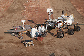 """Two spacecraft engineers join a grouping of vehicles providing a comparison of three generations of Mars rovers developed at NASA's Jet Propulsion Laboratory, Pasadena, California on December 15, 2011. The setting is JPL's Mars Yard testing area.  Front and center is the flight spare for the first Mars rover, Sojourner, which landed on Mars in 1997 as part of the Mars Pathfinder Project. On the left is a Mars Exploration Rover Project test rover that is a working sibling to Spirit and Opportunity, which landed on Mars in 2004. On the right is a Mars Science Laboratory test rover the size of that project's Mars rover, Curiosity, which is on course for landing on Mars in August 2012.  Sojourner and its flight spare, named Marie Curie, are 2 feet (65 centimeters) long. The Mars Exploration Rover Project's rover, including the """"Surface System Test Bed"""" rover in this photo, are 5.2 feet (1.6 meters) long. The Mars Science Laboratory Project's Curiosity rover and """"Vehicle System Test Bed"""" rover, on the right, are 10 feet (3 meters) long.  The engineers are JPL's Matt Robinson, left, and Wesley Kuykendall. The California Institute of Technology, in Pasadena, operates JPL for NASA. .Mandatory Credit: Thomas A. Dutch Slager - NASA/JPL-Caltech via CNP"""