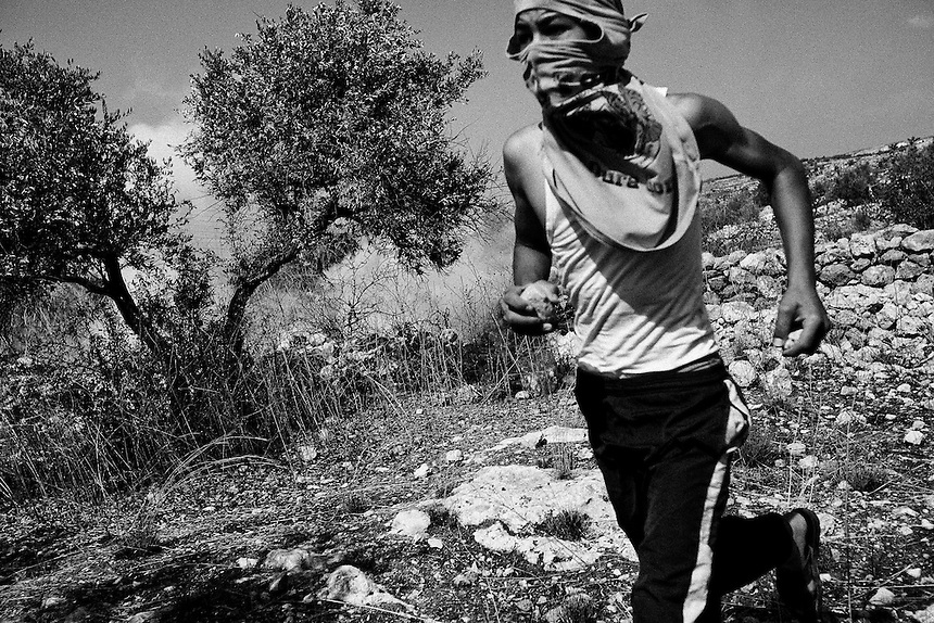 Clutching a stone, a Palestinian boy runs away from an exploding tear gas canister fired by Israeli soldiers during protests at Bil'in, The West Bank, October 2009. Photo: Ed Giles.