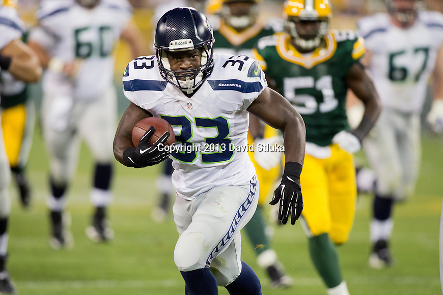 Seattle Seahawks running back Christine Michael (33) scores a touchdown on a long run during an NFL preseason week 3 football game against the Green Bay Packers Thursday, August 23, 2013, in Green Bay, Wis. The Seahawks won 17-10 . (Photo by David Stluka)