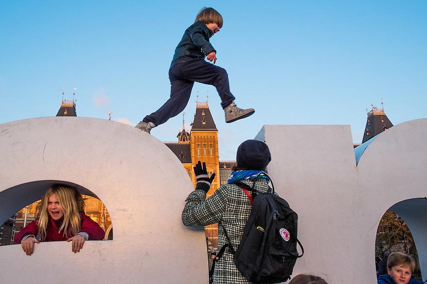 Nederland, Amsterdam, 4 jan 2015<br /> Kinderen springen over de letters van het Amsterdam Logo I Amsterdam op het museumplein. Daarachter het Rijksmuseum<br /> <br /> <br /> Foto: (c) Michiel Wijnbergh