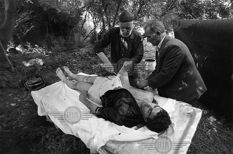 Two elderly men wash the body of a young man who was killed in a mortar attack, before his funeral.  The town borders the Armenian-populated Nagorno Karabakh.