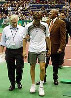 Ferrero verlaat ondersteund door fysio Leo Taal en toernooi directeur Stanley Franken het sportpaleis nadat hij door een enkel blessure moest opgeven