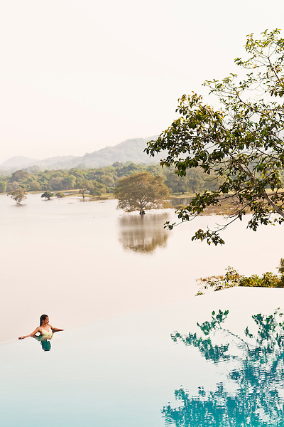 Woman in Infinity Pool at Heritance Kandalama Hotel, Dambulla, Sri Lanka. A woman bathes in the Infinity Pool overlooking Kandalama Lake at Heritance Kandalala Hotel. The Infinity Pool is one of three swimming pools at the hotel, designed by Sri Lankan architect Geoffrey Bawa.