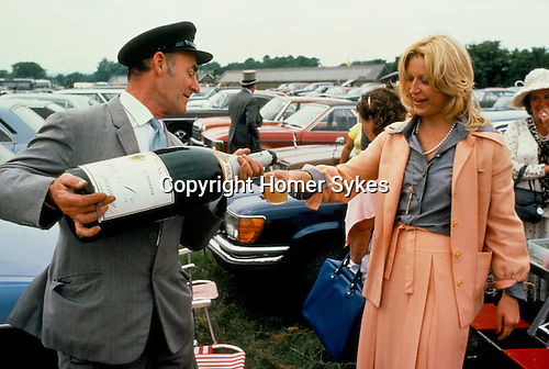 CHAUFFEUR SERVING GLASS OF CHAMPAGNE FROM AN EXTRA LARGE BOTTLE FOR WOMAN AT THE DERBY DAY HORSE RACES,
