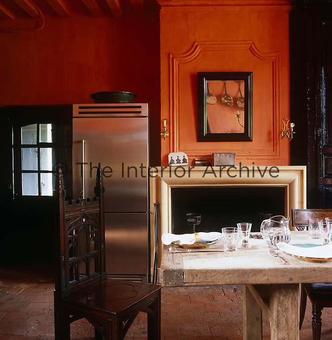 A modern stainless steel fridge stands next to the open fireplace in this burnt orange painted kitchen