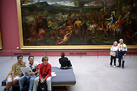 The Louvre. People viewing paintings.