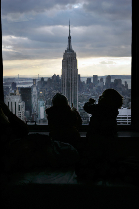 Cousins Melina Gnugesser, 4, from Toronto, and Miro Gnugesser, also 4, from White Plains, enjoy the view of NYC and the Empire State Building from the TOP OF THE ROCK Observation Deck.
