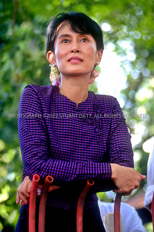 6/8/1996--Yangon, Myanmar (Rangoon, Burma)..Burmese opposition democracy leader Aung San Suu Kyi speaks to followers outside her home on University Avenue. in Rangoon Burma...Aung San Suu Kyi (born 19 June 1945) is a Burmese opposition politician and a former General Secretary of the National League for Democracy (NLD). In the 1990 general election, Aung San Suu Kyi's National League for Democracy party won 59% of the national votes and 80% (392 of 492) of the seats in Parliament, leading some to claim that this implies Suu Kyi was elected Prime Minister. She had, however, already been detained under house arrest before the elections. She has remained under house arrest in Myanmar for almost 14 out of the past 20 years...Aung San Suu Kyi was the recipient of the Rafto Prize and the Sakharov Prize for Freedom of Thought in 1990 and the Nobel Peace Prize in 1991. In 1992 she was awarded the Jawaharlal Nehru Award for International Understanding by the Government of India. Aung San Suu Kyi is the third child and only daughter of Aung San, considered to be father of modern-day Burma...All photographs ©2010 Stuart Isett.All rights reserved. This image may not be reproduced without expressed written permission from Stuart Isett.
