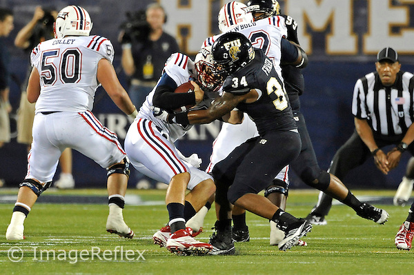 12 November 2011:  FIU linebacker Winston Fraser (34) sacks Florida Atlantic quarterback Graham Wilbert (14) in the third quarter as the FIU Golden Panthers defeated the Florida Atlantic University Owls, 41-7, to win the annual Shula Bowl game, at FIU Stadium in Miami, Florida.