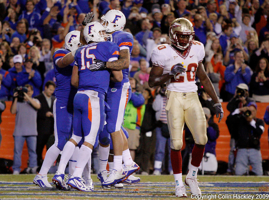 GAINESVILLE, FL 11/28/09-FSU-UF FB09 CH39-Florida State's Jamie Robinson walks out of the endzone as Florida's Tim Tebow celebrates his touchdown during second half action Saturday at Florida Field in Gainesville. The Gators beat the Seminoles 37-10..COLIN HACKLEY PHOTO