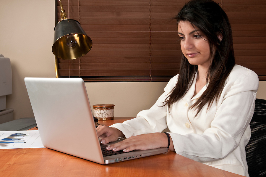 Young woman working at computer in office desk, in small business.