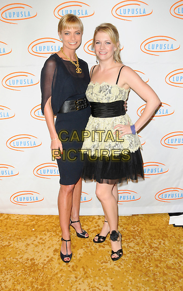 JAIME PRESSLY & MELISSA JOAN HART.arriving at Lupus LA's 7th Annual Bag Ladies Luncheon to raise funds for lupus research at the Beverly Wilshire Four Seasons Hotel in Beverly Hills, California, USA, .November 18th, 2009..full length Jamie Pressley black navy blue sheer dress waist belt t-bar peep toe shoes gold chunky Chanel logo double c's necklace hand on hip see through thru ankle strap flower sandals rosette chains pale yellow lace black tulle .CAP/ROT.©Lee Roth/Capital Pictures