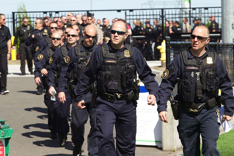 Portland Police Bureau Officer Shawn Gore, right, leads K-9 officers from local police agencies into Hillsboro Stadium for a public tribute to Portland Police Bureau's Canine, Mick.<br /> Photo by Jaime Valdez