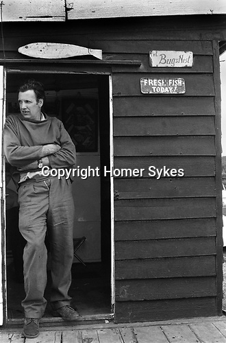 Dunwich, Suffolk. 1973<br /> A fisherman sells todays fresh fish from The Bugs Nest. In Anglo Saxon times Dunwich was the capital of the Kingdom of the East Angles, a port the size of 14th century London. Almost nothing now remains.