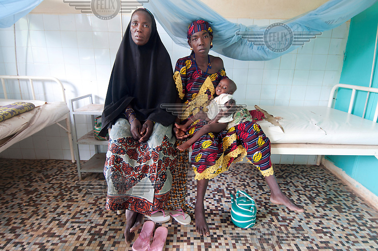 Grandmother Hadja and Safi with her baby Edwan, 13 months old sit together in CRENI (Centre de Recuperation Nutritionnelle Intensive, a therapeutic feeding centre) in Dosso where Edwan is being treated for malnutrition. A drought in southern Niger has affected up to 8 million people.