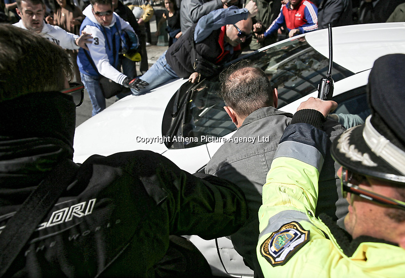 """Pictured: Taxi drivers attack an Uber cab in Syntagma Square, Athens Greece. Tuesday 06 March 2018<br /> Re: Taxi drivers have attacked Uber vehicles while protesting against Uber operating in Athens, Greece.<br /> Taxi drivers will on strike for nine hours on Tuesday8 a.m. to 5 p.m. in protest at what they call unfair competition from Uber taxi services.<br /> In a statement, the SATA union representing cab drivers in Attica also expressed dismay at delays in passing a Transport Ministry bill to reorganize their sector and derided """"innovative platforms that rob taxi drivers and the country."""""""