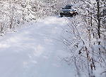 Volvo XC70 car on a snow covered unpaved country road, winter nature scenic.