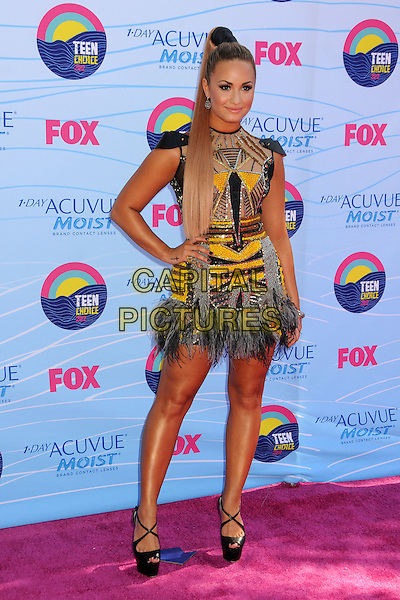 Demi Lovato.FOX's 2012 Teen Choice Awards held at The Gibson Ampitheatre in Universal City, California, USA..July 22nd, 2012.full length beige yellow gold black beads beaded dress ponytail sequins sequined hand on hip feathers grey gray.CAP/ADM/BP.©Byron Purvis/AdMedia/Capital Pictures.