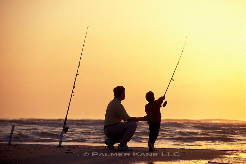 Father and son surf fish on Carolina's Cape Fear, Bald Head Island, North Carolina, USA