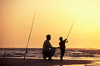 Father and son surf fish on Carolina's Cape Fear, Bald Head Island, North Carolina, USA