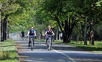 Two young women cycle by the coastal path enjoying the sunshine in Swansea, Wales, UK Friday 13 May 2016