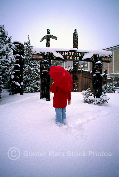 Woman standing in Snow at  Totem Poles in Thunderbird Park, Victoria, Vancouver Island, British Columbia, Canada, in Winter (Model Released)