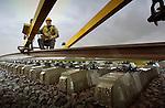 TIEL - Langs de Betuweroute bij Tiel wordt op een bijzondere manier door Strukton gewerkt aan nieuw spoor. Met behulp van nieuwe spoorlegtrein wordt zonder werkspoor de rails op de betonnen staven gelegd daarbij rijdend over het nieuwe spoor. Met deze methode is het mogelijk 2 x zo snel nieuw spoor aangelegd, ruim een kilometer per dag. Volgens projectorganisatie Betuweroute is deze sneller manier van spoorbouw in Nederland nog niet eerder vertoond. COPYRIGHT TON BORSBOOM.