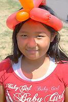 Happy Asian American girl age 8 wearing a balloon twist hat. Dragon Festival Lake Phalen Park St Paul Minnesota USA