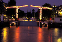 drawbridge, Amsterdam, Holland, Netherlands, Noord-Holland, Europe, Drawbridge illuminated at night on a canal in Amsterdam.