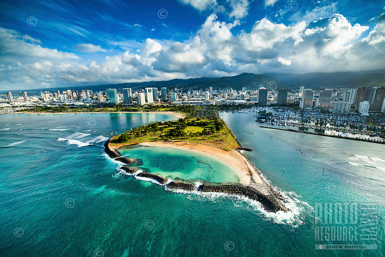 An aerial view of O'ahu's Magic Island at sunrise, with Ala Moana Beach Park and Ala Wai Yacht Harbor in the background.