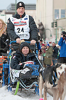 Jason Campeau and team leave the ceremonial start line with an Iditarider at 4th Avenue and D Street in downtown Anchorage, Alaska on Saturday, March 5th during the 2016 Iditarod race. Photo by Joshua Borough/SchultzPhoto.com