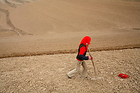 IFADHuinin_040 18-year-old  Nan Yanshuang walking in a large dry field in Linfang Village, Zhaisuo Township, Huinin County, Gansu Province on 20th March 2006.