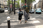 Backs of mother with headscarf and daughter with school bags walking towards metro. Paris, France.
