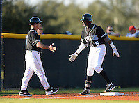 Olympia Titans shortstop Nick Gordon (5) is congratulated by head coach Chuck Schall (7) after hitting a triple during a game against the Orangewood Christian Rams at Olympia High School on February 19, 2014 in Olympia, Florida.  (Mike Janes/Four Seam Images)