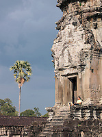 A local man sits by an entrance way to Angkor Wat, Angkor, Siem Reap Province, Cambodia